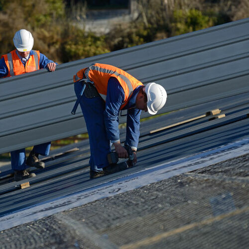 Roofers Work on a Commercial Metal Roof