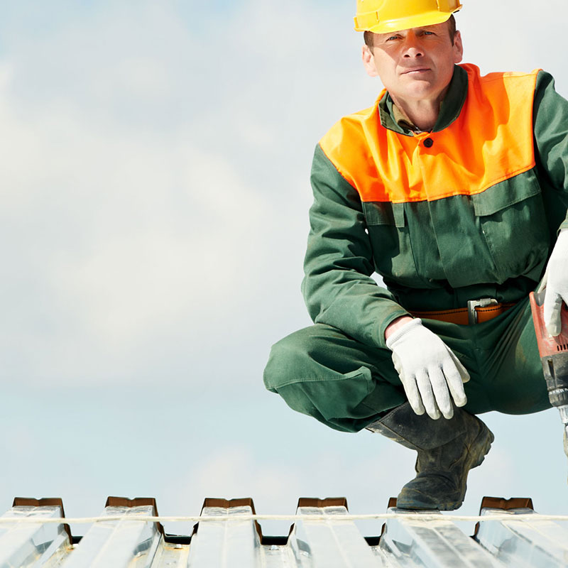 Commercial Roof Contractor on a Metal Roof with a Drill and Hard Hat