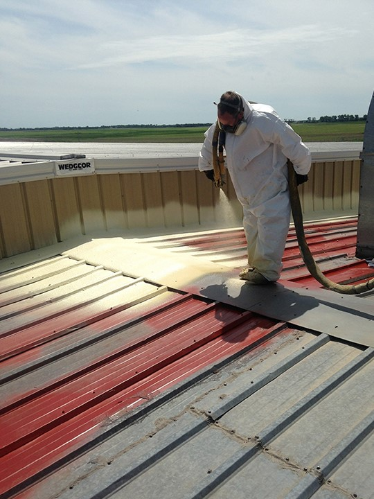 Contractor Repairs Metal Roof With Coating