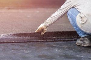 Worker Performs Roof Restoration